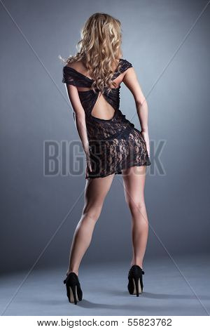 Slender curly blonde posing in black lace negligee