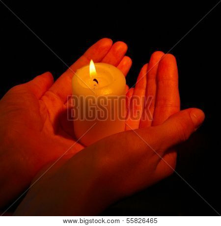 Burning candle in hands isolated on black