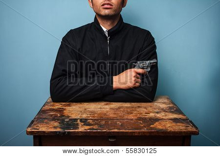 Thug At Table With Gun