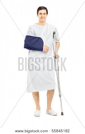 Full length portrait of a smiling male patient in hospital gown with broken arm holding a crutch isolated on white background