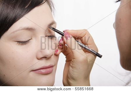 Makeup artist in the process of makeup brings eyebrow pencil model
