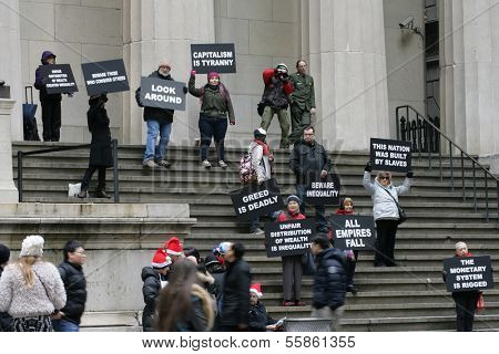 NEW YORK - DEC 19: Protestors hold signs while standing on the steps of Federal Hall in lower Manhattan near the New York Stock Exchange on Dec  19, 2013 in New York City.