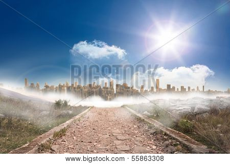 Stony path leading to large urban sprawl under the sun