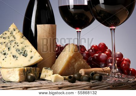 Refined still life of wine, cheese and grapes on wicker tray on wooden table on blue background