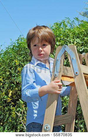 The beautiful green-eyed boy spoiled by attention climbed up a wooden sliding ladder and doesn't want to go down