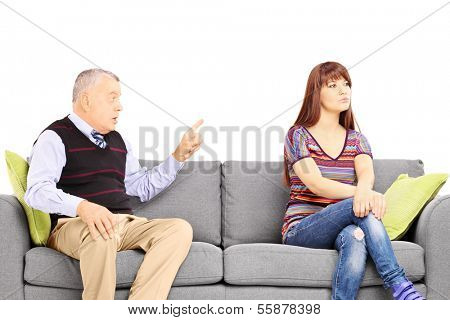 Father reprimending his uninterested daughter seated on a sofa isolated against white background