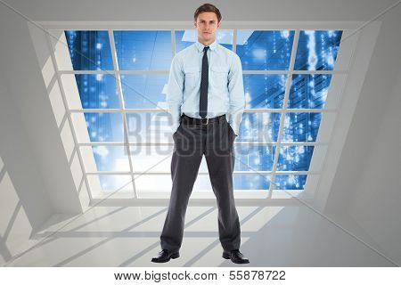 Serious businessman standing with hands in pockets against server hallway seen through window