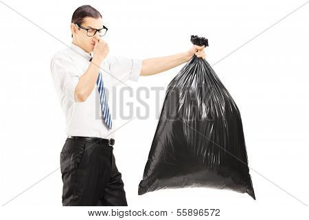 Male closing his nose and carrying a stinky garbage bag isolated on white background