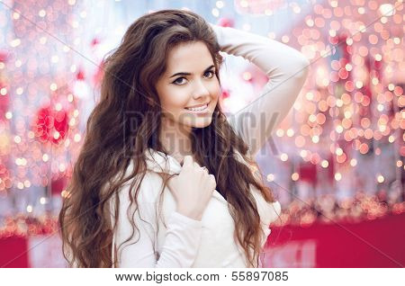 Christmas Happy Smiling Teen Girl Over Xmas Background. Young Woman With Long Curly Hair.