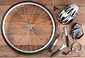 Overhead view of bicycle gear laid out on a rustic wooden floor. Items include, Wheel, pump, gloves,