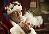 stock photo of frown  - Portrait of a frowning Bad Santa smoking a joint - JPG