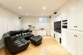 stock photo of basement  - Finished basement of residential home with entertainment center couch and television - JPG