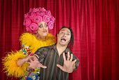 stock photo of drag-queen  - Big drag queen trying to kiss a scared man - JPG