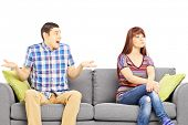 Young couple sitting on a sofa during an argument isolated on white background