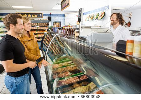 Smiling mid adult salesman attending customers at butcher's shop