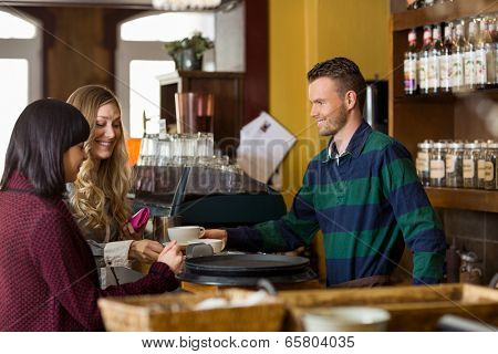 Handsome bartender serving coffee to women at counter in cafe