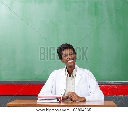Portrait of happy African American female teacher sitting at desk in classroom