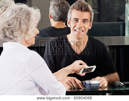 Portrait of happy hairdresser with woman paying through mobile phone at counter using NFC