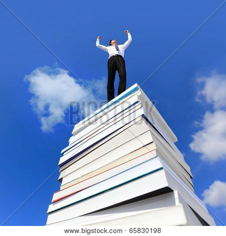 Knowledge is power  , business man arise arm  on a stack Of Books