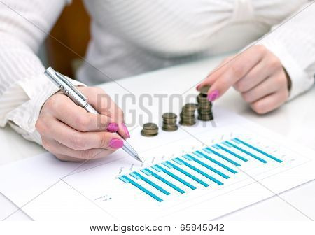 Woman stacks coins. Counting every penny.