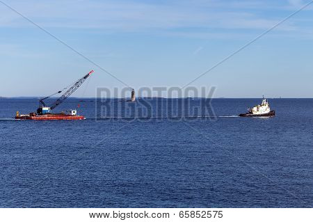 Portland, Maine - Tug boat towing a barge in front of Ram Island Ledge Light