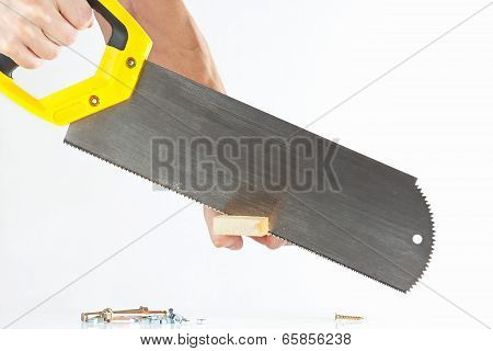 Hand of a workman cutting a wooden block with a handsaw on white background