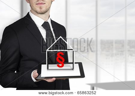 businessman holding tablet paragraph house