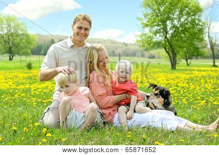 Happy Family Relaxing Outside In Field Of Flowers With Dog