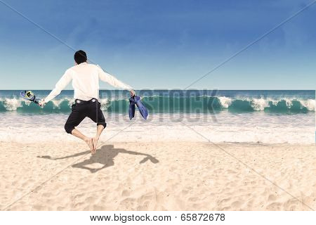 Backside Of Businessman Jumping On Beach
