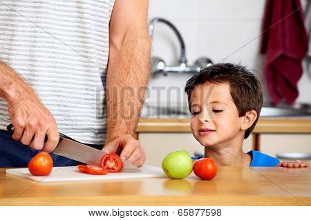 inquisitive young boy watches father slicing tomato in kitchen