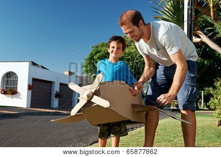 son and dad playing with toy airplane in the garden at home having fun together and smiling