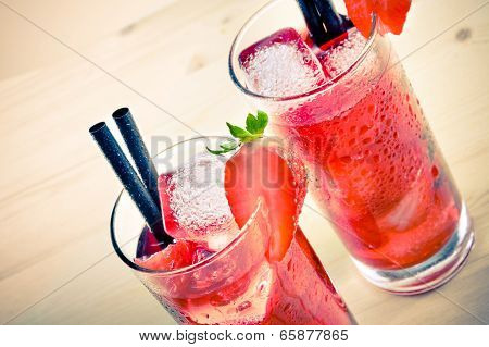 Two Glasses Of Strawberry Cocktail With Ice On Old Wood Table, Old Style