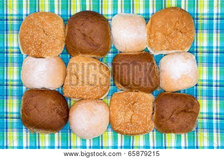 Assorted Hamburger Rolls On A Checked Picnic Cloth