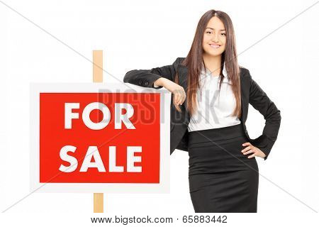 Female realtor leaning on a for sale sign isolated on white background