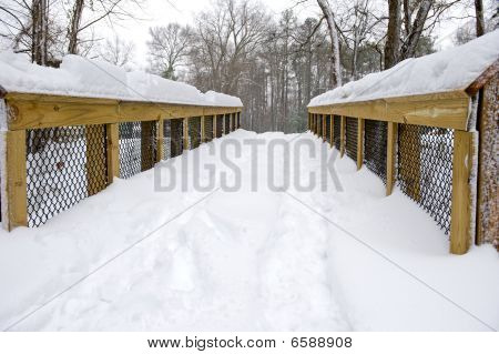 Snow covered bridge in a rural town during winter.