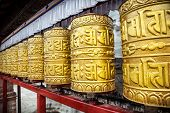 stock photo of nepali  - Golden prayer wheels at Swayambhunath stupa in Kathmandu Nepal - JPG