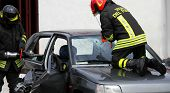 stock photo of firehouse  - firefighters in action while they open the car after the accident to the driver - JPG