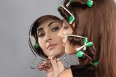 stock photo of hair curlers  - girl with hair curlers looking in the mirror - JPG
