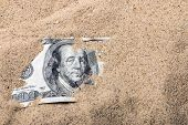 stock photo of sand dollar  - 100 dollar bill buried in the sand - JPG
