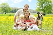 stock photo of shepherd dog  - Portrait of a happy family of four people including mother father young child and baby sitting outside with their German Shepherd mix dog on a Spring day - JPG
