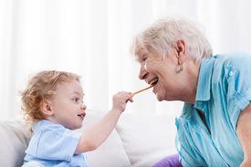foto of grandma  - Grandson and his grandma eating together horizontal - JPG
