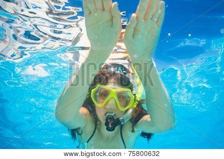 Woman wears snorkeling mask swimming underwater
