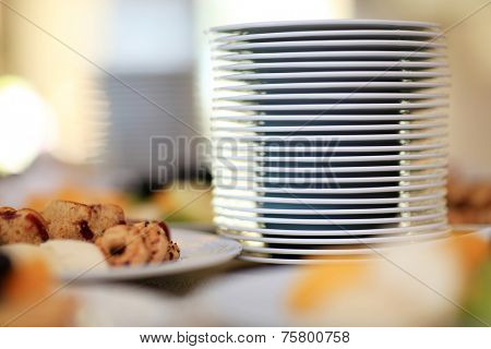 Stack of plates on table. Breakfast food. Shallow DOF