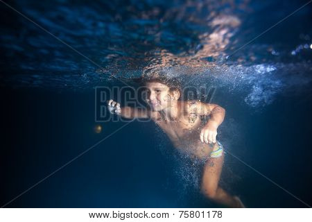 Small boy swimming underwater in pool at night