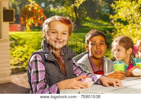 Multinational children sit together at table