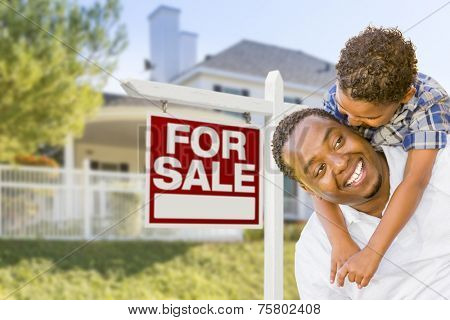 African American Father and Mixed Race Son In Front of Home For Sale Real Estate Sign and New House.