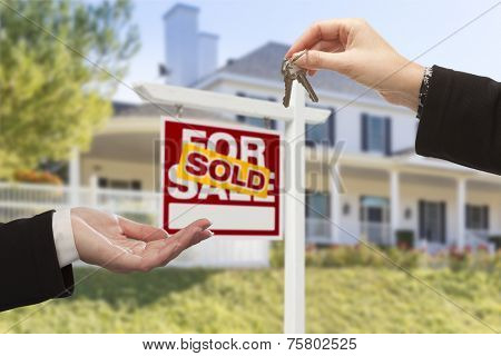 Agent Handing Over Keys to a New Home with Sold Real Estate Sign and House in the Background.