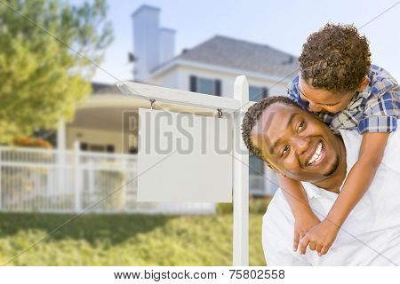 Happy African American Father and Mixed Race Son In Front of Blank Real Estate Sign and New House.