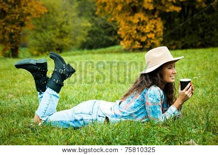 smiling young woman enjoy in coffee break in nature, lie on grass in park, wearing hat, blue torn jeans and tartan shirt, full body shot