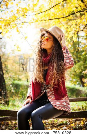 young woman with long curly hair wearing hat,  sunglasses, coat and  red scarf sit on wooden fence in park, sunny autumn day